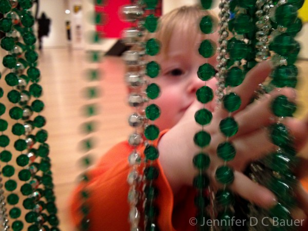 Addison examining the beads hanging in a doorway at the Boston MFA.