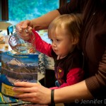 Addie pouring water into the Mountain House Mountain Oven.