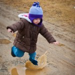 Addie jumping in mud puddles at Appleton Farms in Ipswich, MA
