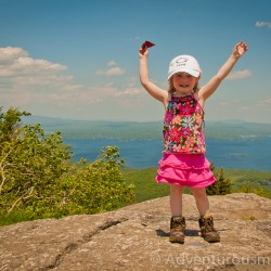 Addie standing on the summit marker of Mt. Major in Alton, NH