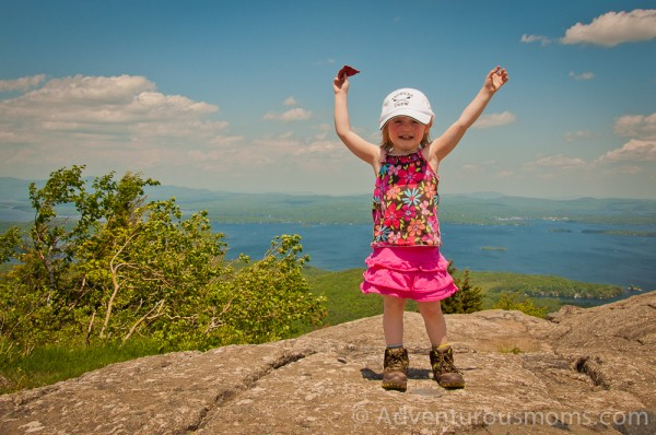 Addie standing on the summit marker of Mt. Major in Alton Bay, NH