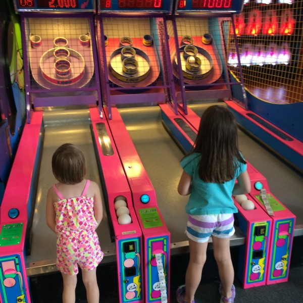 Addie and Bria playing skeeball
