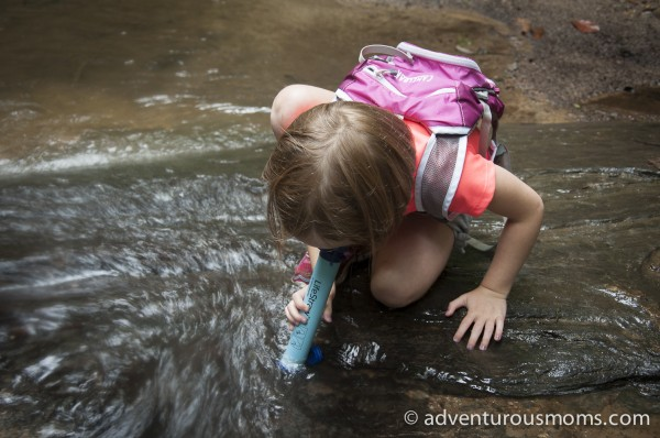 Addie using a  LifeStraw Personal Water Filter